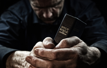 A tired and hopeless person is praying while holding the Bible in his hands.